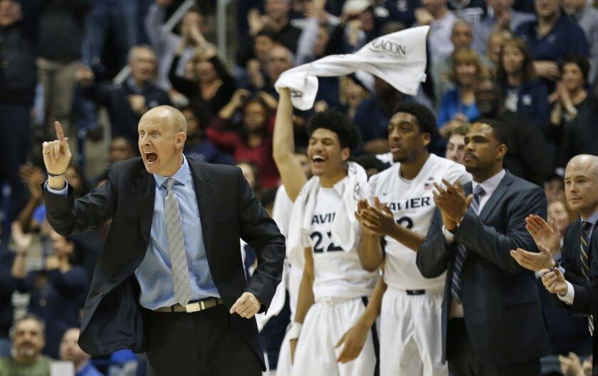 Xavier head coach Chris Mack directs his team during the second half of an NCAA college basketball game against Marquette Saturday, Feb. 6, 2016, in Cincinnati. Xavier won 90-82. (AP Photo/Gary Landers)