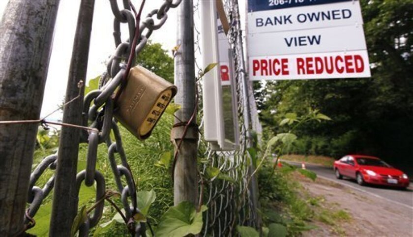 "In this June 9, 2011 photo, a ""bank-owned view price reduced,"" lot is chained and locked but advertised for sale, in Seattle. Two years after economists say the Great Recession ended, the recovery has been the weakest and most lopsided of any since the 1930s. (AP Photo/Elaine Thompson)"
