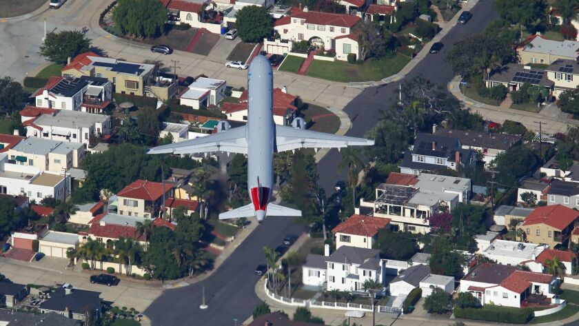 An American Airlines jet takes off from San Diego International Airport over Point Loma.