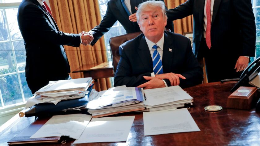 President Donald Trump sits at his desk after a meeting with Intel CEO Brian Krzanich, left, and mem