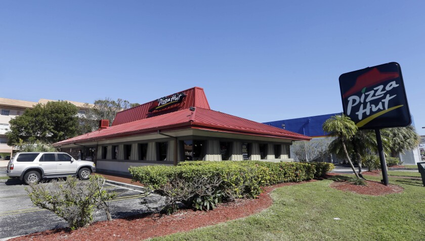 FILE- This Jan. 24, 2017, file photo shows a Pizza Hut in Miami. Pizza Hut has reached an agreement with one of its largest franchisees to close 300 underperforming U.S. restaurants. NPC International, a Leawood, Kansas-based franchisee, announced the agreement Monday, Aug. 17, 2020, in a bankruptcy court filing. (AP Photo/Alan Diaz, File)
