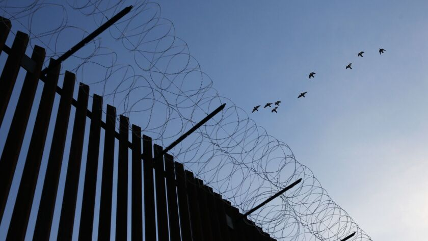 CALEXICO, CA-APRIL 3, 2019: Birds fly over a newly completed section of the border fence on April 3,
