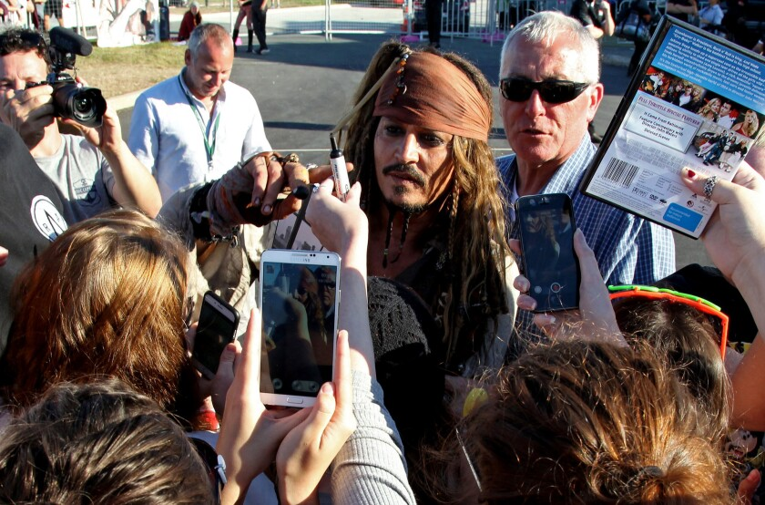 """Johnny Depp, in costume as Captain Jack Sparrow, greets Australian fans after a day on the set filming the fifth movie in the """"Pirates of the Caribbean"""" series on June 4, 2015."""