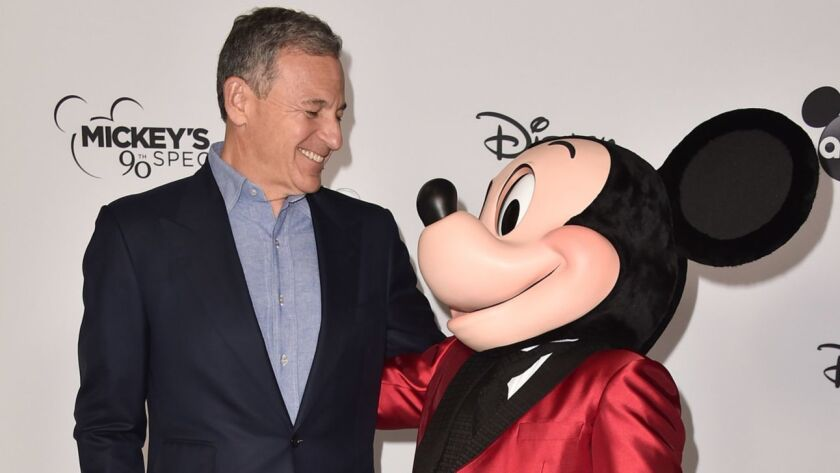 Disney CEO Bob Iger smiles at Mickey Mouse at a Saturday event.