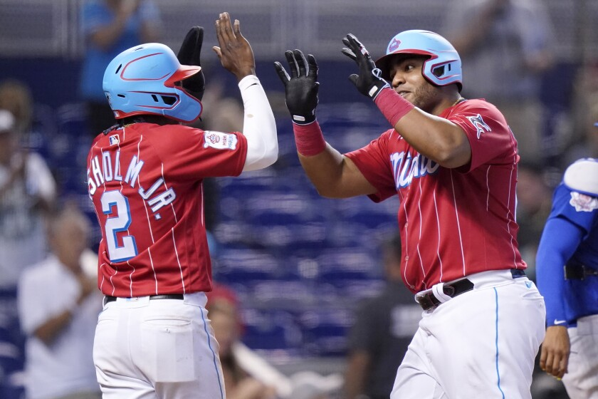 Miami Marlins' Jazz Chisholm Jr. (2) greets Jesus Aguilar after they scored on a two-run home run hit by Aguilar during the eighth inning of a baseball game against the Chicago Cubs, Sunday, Aug. 15, 2021, in Miami. (AP Photo/Lynne Sladky)
