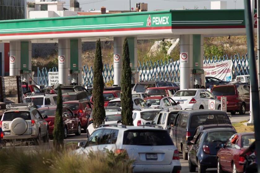 Fotografía del 23 de diciembre de 2016 unos conductores formando una fila para comprar gasolina ante la escasez del combustible en la ciudad mexicana de Morelia. Al menos una decena de estados de México padecen en los últimos días un serio problema de desabastecimiento de gasolina, que la firma estatal Petróleos Mexicanos (Pemex) atribuye a las tomas clandestinas de combustible. EFE