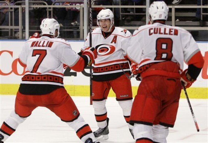 Carolina Hurricanes' Ray Whitney, center, celebrates with teammates Matt Cullen (8) and Niclas Wallin (7) after scoring the game-winning goal during the overtime period of an NHL hockey game against the New York Rangers, Saturday, Jan. 2, 2010, in New York. The Hurricanes won the game 2-1. (AP Photo/Frank Franklin II)