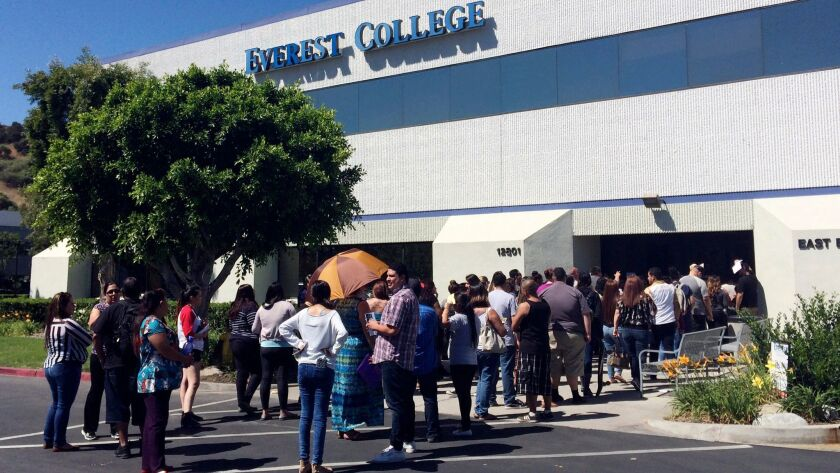 FILE - In this April 28, 2015, file photo, students wait outside Everest College in Industry, Calif.