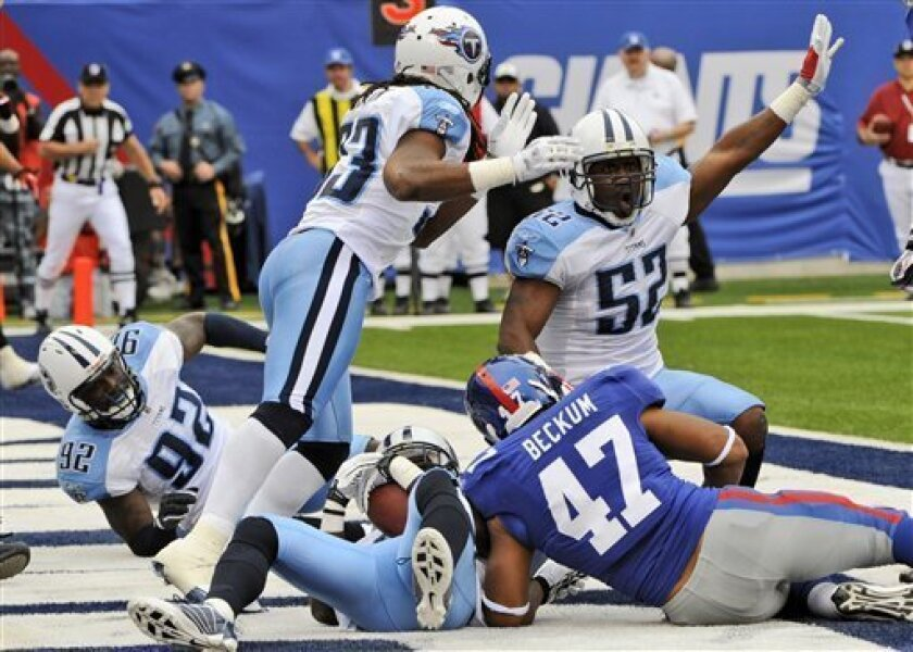 Tennessee Titans Linebacker Jamie Winborn (52) celebrates after teammate Jason McCourty, bottom center, intercepted a pass for a touchback during the first quarter of an NFL football game as New York Giants' Travis Beckum (47) looks on at New Meadowlands Stadium, Sunday, Sept. 26, 2010, in East Rutherford, N.J. (AP Photo/Bill Kostroun)