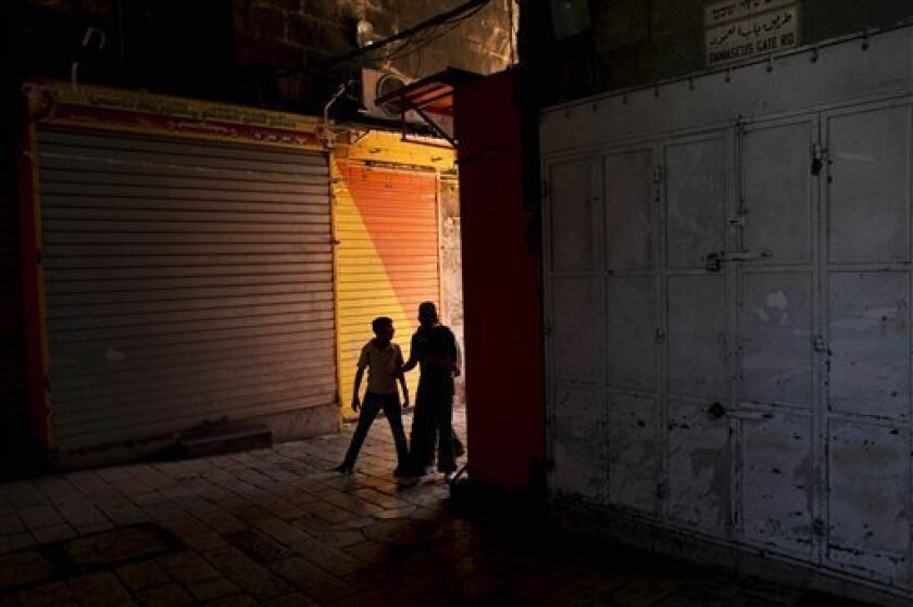 A Palestinian woman and youth pass in front of shops closed as part of a general strike by Palestinians to protest against the Israeli naval commando raid on a flotilla attempting to break the blockade on Gaza, inside Damascus gate, in Jerusalem's Old City, Tuesday, June 1, 2010. Activists seized b
