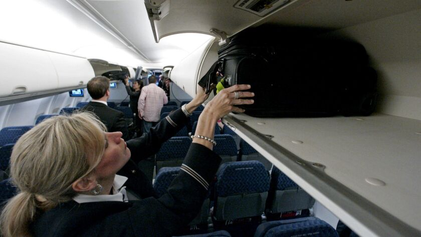 An American Airlines flight attendant demonstrates the overhead baggage area.