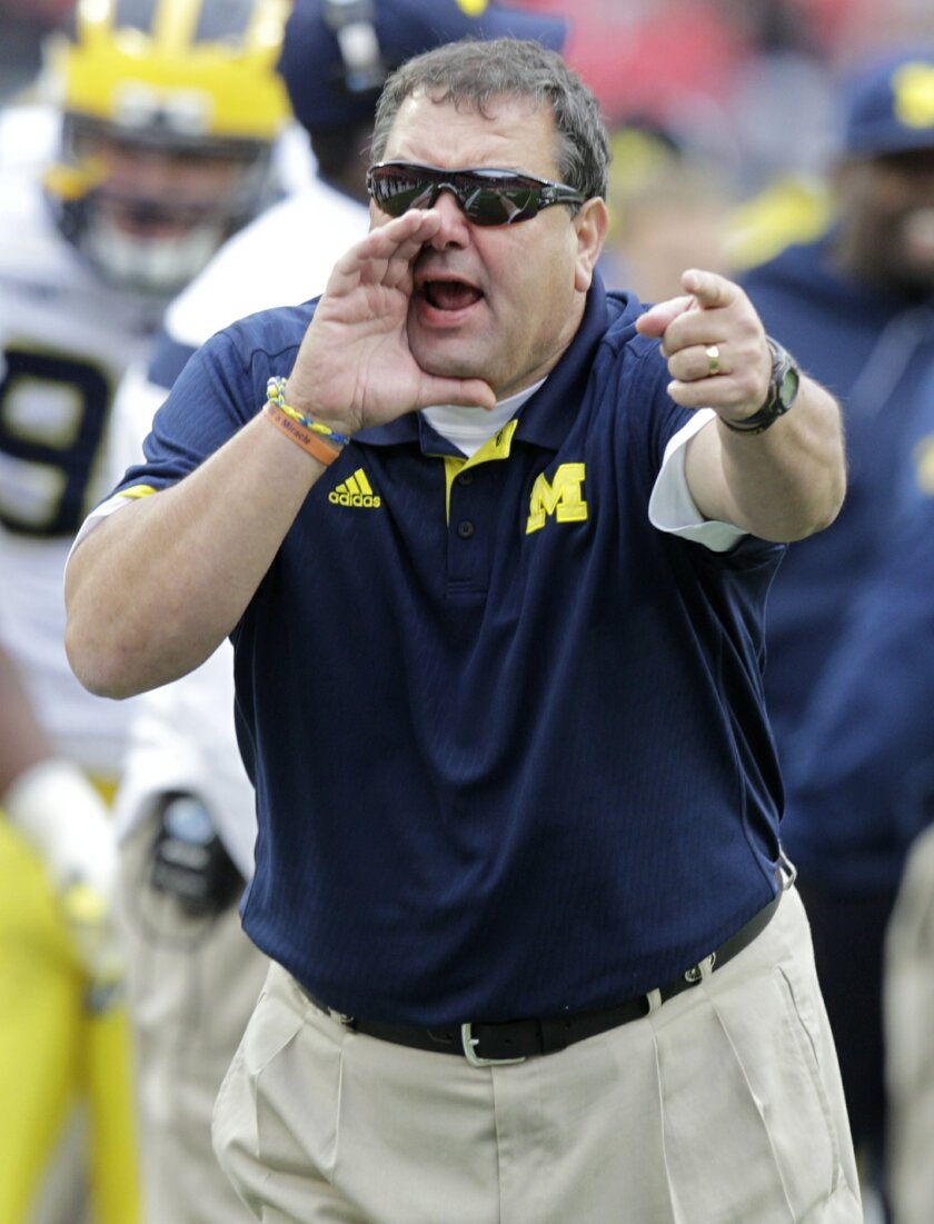 Michigan head coach Brady Hoke shouts to his team as they play against Ohio State in the third quarter of an NCAA college football game Saturday, Nov. 29, 2014, in Columbus, Ohio. Ohio State beat Michigan 42-28. (AP Photo/Jay LaPrete)