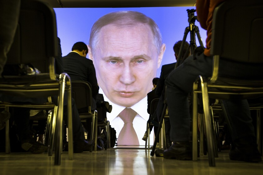 Journalists watch as Russian President Vladimir Putin gives his annual state of the nation address in Moscow on March 1.