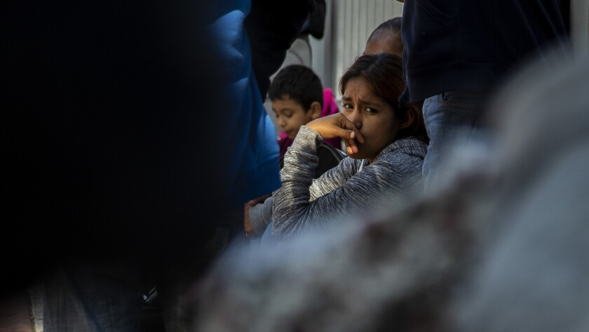 TIJUANA, MEXICO - JUNE 20, 2018: An immigrant girl sits with her family members at the border whil