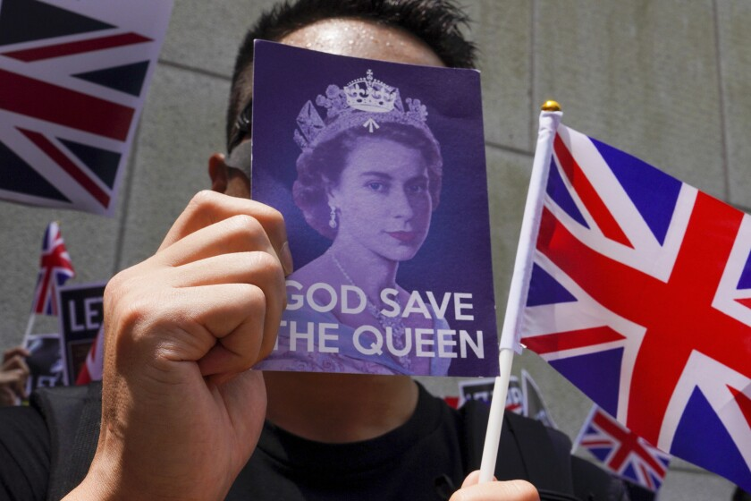 FILE- In this Sunday, Sept. 15, 2019 file photo, a protester uses a placard to block his face as they participate in a peaceful demonstration outside the British Consulate in Hong Kong. The British government said Thursday, April 8, 2021, it is setting up a 43 million pound ($59 million) fund to help migrants from Hong Kong settle in the country as they escape increasing political repression in the former colony. (AP Photo/Vincent Yu, File)