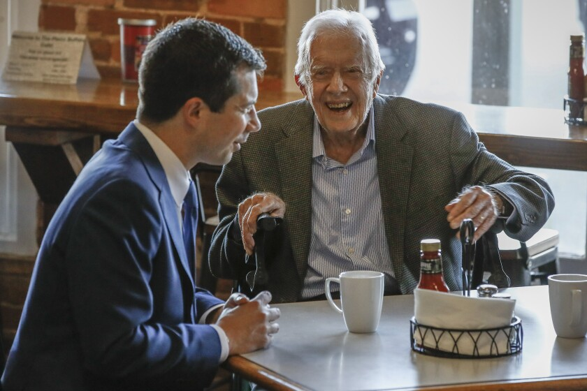 Democratic presidential candidate former South Bend, Ind., Mayor Pete Buttigieg, left, meets with former President Jimmy Carter, center, at Buffalo Cafe in Plains, Ga., Sunday, March 1, 2020. (AP Photo/Matt Rourke)