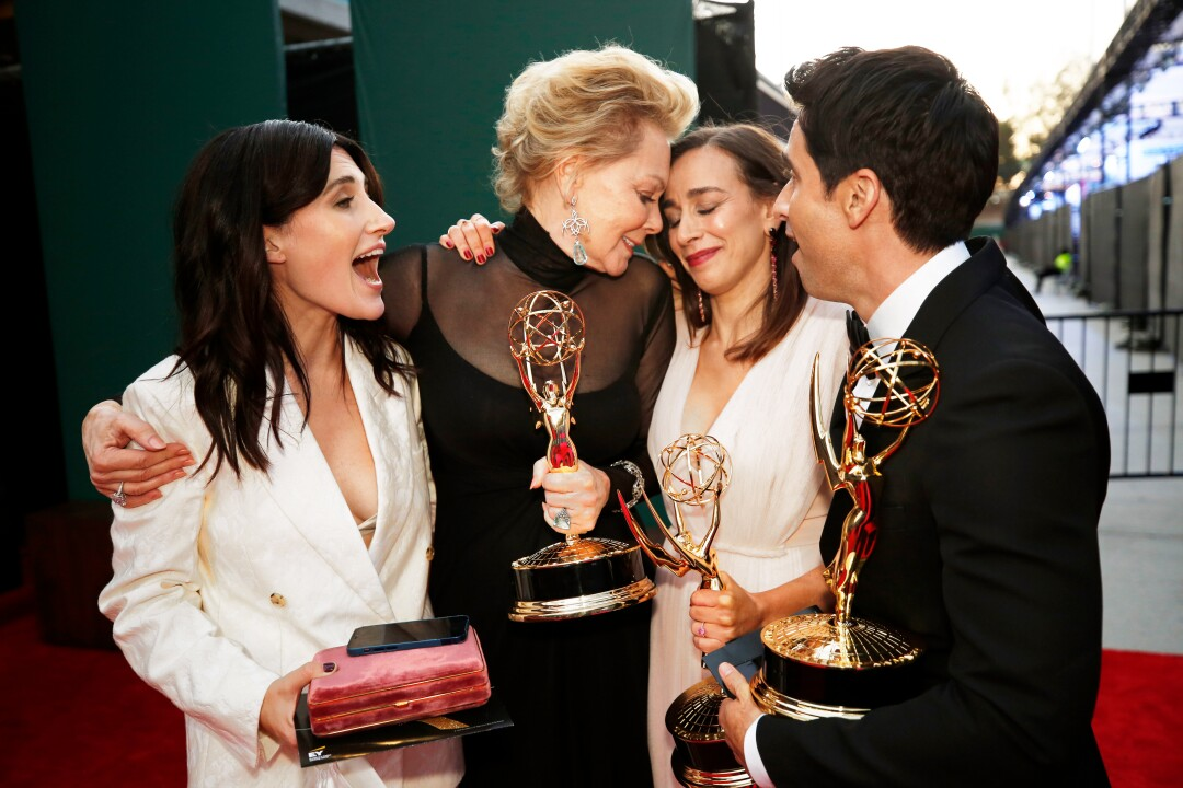 Three women and a man, right, stand shoulder to shoulder. Three of them are holding statuettes