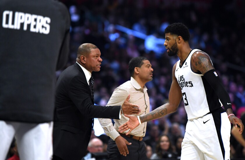 Clippers coach Doc Rivers and forward Paul George slap hands during the first half of a game against the Rockets on Dec. 19 at Staples Center.