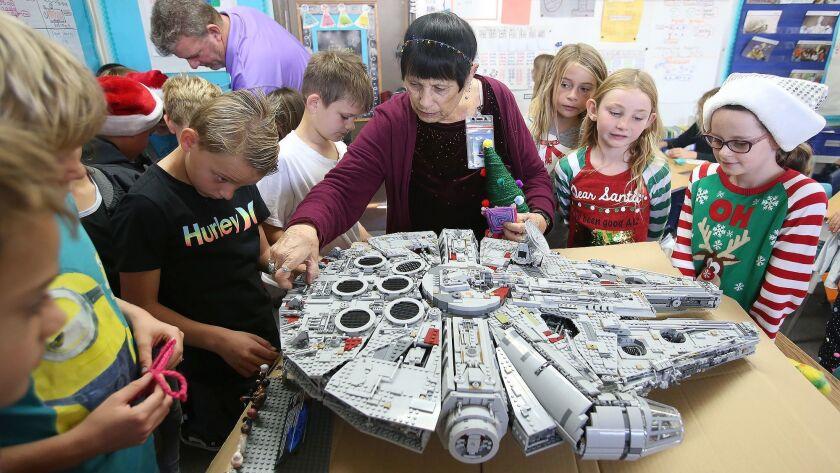 Instructional assistant Jeanna Bassett looks at her rebuilt Star Wars Millennium Falcon ship, made o