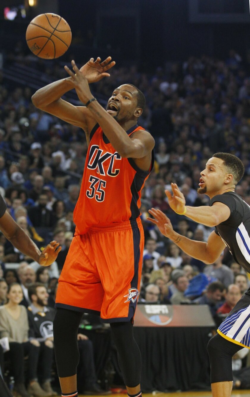 Oklahoma City Thunder's Kevin Durant, left, shoots as Golden State Warriors' Stephen Curry defends during the first half of an NBA basketball game, Saturday, Feb. 6, 2016, in Oakland, Calif. (AP Photo/George Nikitin)