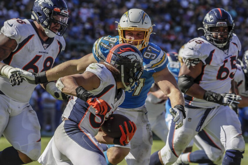 Chargers defensive end Joey Bosa (97) closes  on Denver Broncos running back Phillip Lindsay (30) during third-quarter action at Dignity Health Sports Park on Sunday.