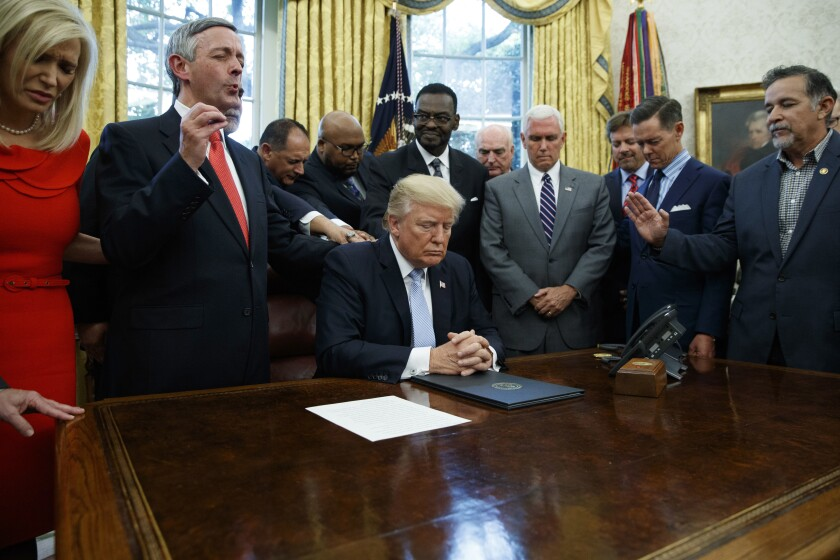 FILE - In this Sept. 1, 2017 file photo, religious leaders pray with President Donald Trump after he signed a proclamation for a national day of prayer to occur on Sunday, Sept. 3, 2017, in the Oval Office of the White House in Washington. White evangelical Protestants stand noticeably apart from other religious people on how the government should act on two of the most politically divisive issues at play in the 2020 presidential election, according to an early December 2019 poll of Americans from various faith backgrounds. (AP Photo/Evan Vucci, File)
