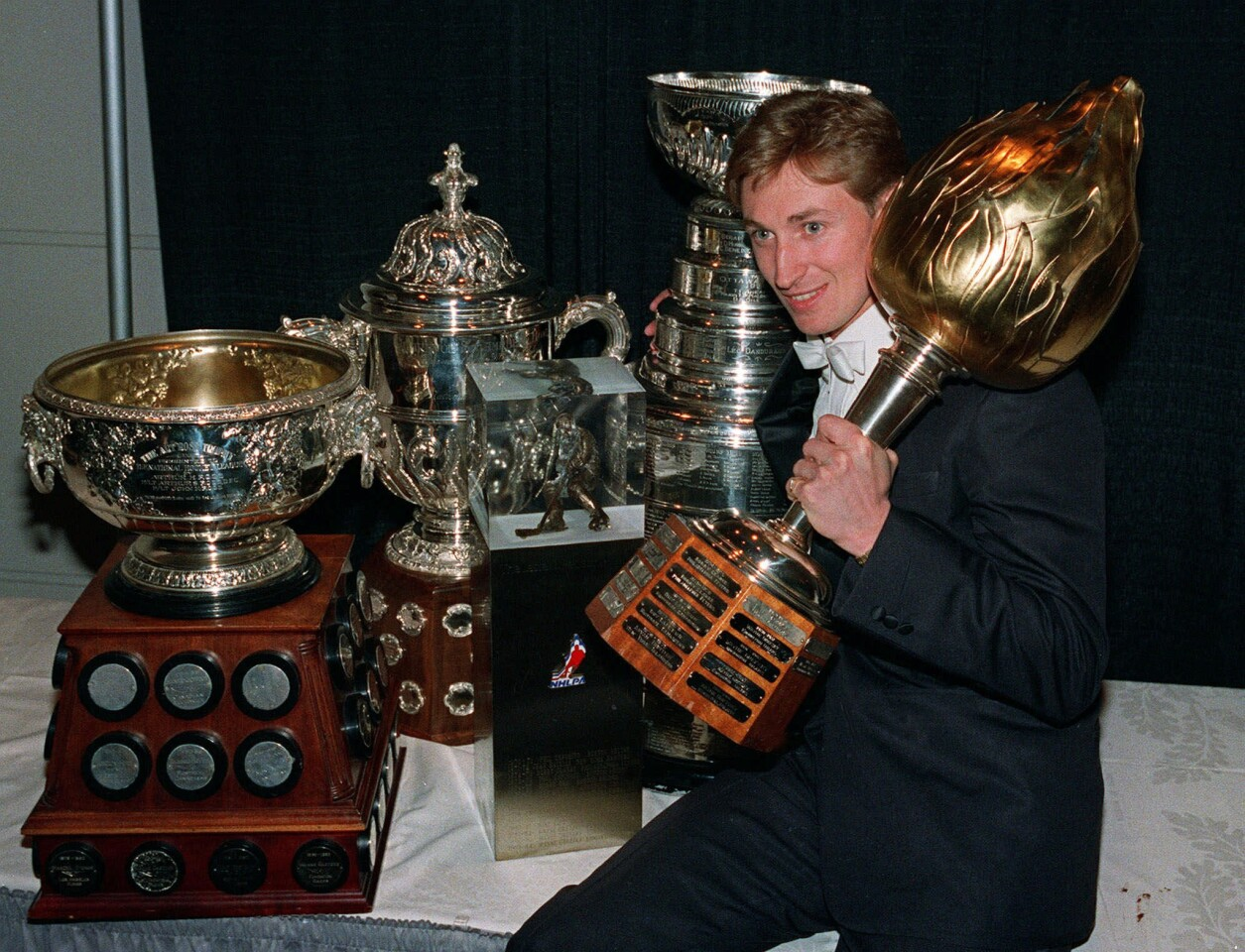 Oilers center Wayne Gretzky celebrates with five NHL trophies after the league awards presentation in Toronto on June 10, 1987. Trophies shown, from left, are Art Ross scoring leader, Campbell Conference winners, Leater B. Pearson selected by players, Lord Stanley's Cup, and Hart Trophy most valuable player.