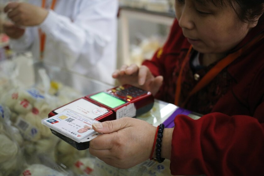 """In this April 1, 2016 photo, a worker swipe the """"Beijing Connect"""" old person's card for a customer at a steamed bread store in a supermarket in Beijing. When people over 80 in Beijing take a bus, see a doctor or spend money, their activities are digitally tracked by the government, as part of an effort to improve services for the country's rapidly growing elderly population. The data amassed with each swipe of the multi-purpose """"Beijing Connect"""" old person's card goes into a massive database of the elderly in the capital. City authorities hope the information will enable them to better cope with their burgeoning population of over-60s, which already stands at 3 million. (AP Photo/Andy Wong)"""