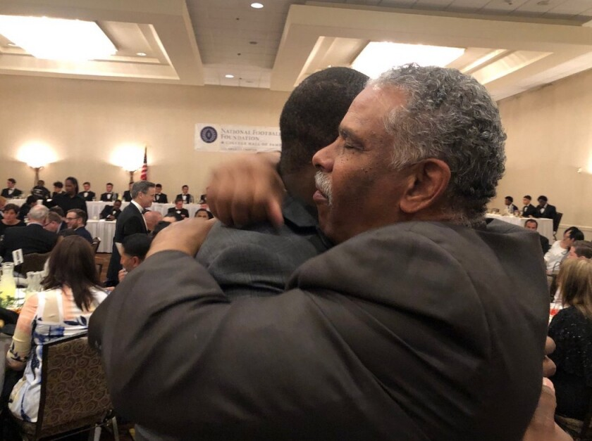 Paul Knox, the football coach at Washington Prep, embraces his former Dorsey player, Johnathan Franklin, at an awards banquet. Knox turns 67 in December and keeps coaching.