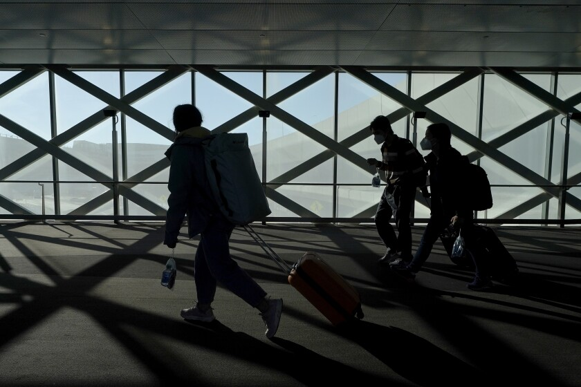 Travelers drag luggage while walking out of a terminal at San Francisco International Airport