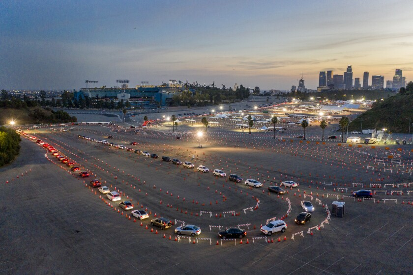 A long line of cars snaking through orange cones in the Dodger Stadium parking lot at dusk.