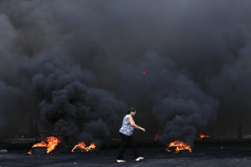 A woman walks past burning tires that were used to block a road during a protest in Beirut on Friday.