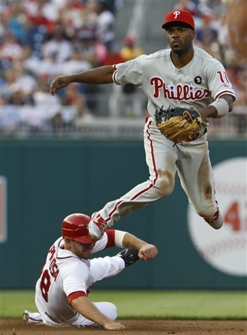 Philadelphia Phillies shortstop Jimmy Rollins, top, leaps to avoid Washington Nationals' Danny Espinosa after forcing him at second base to turn a double play in the second inning of a baseball game, Tuesday, May 31, 2011, in Washington. (AP Photo/Ann Heisenfelt)