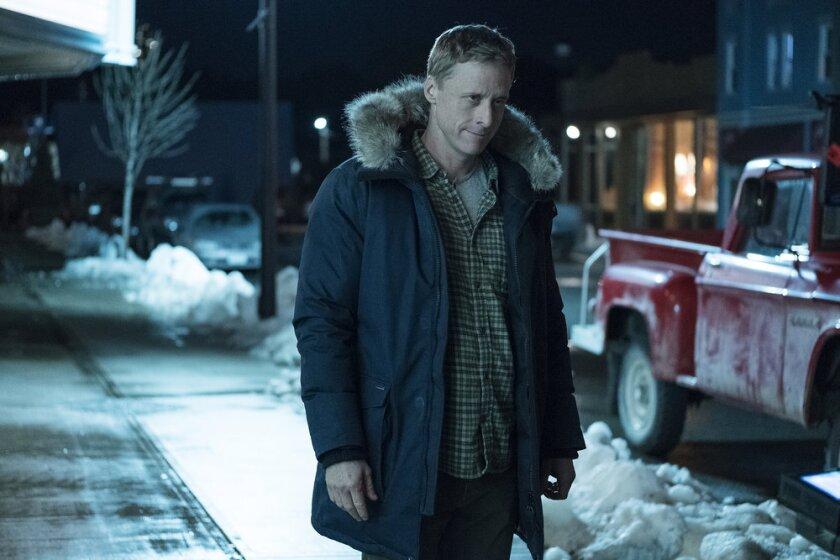 """Alan Tudyk in a parka on a snowy street in Syfy's """"Resident Alien."""""""