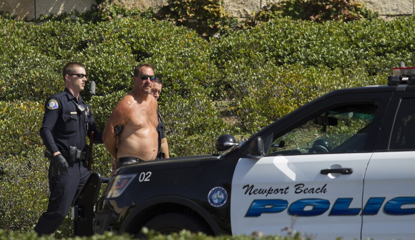 Newport Beach Police officers arrest a man after he engaged in pushing anti Trump and Pence protesto