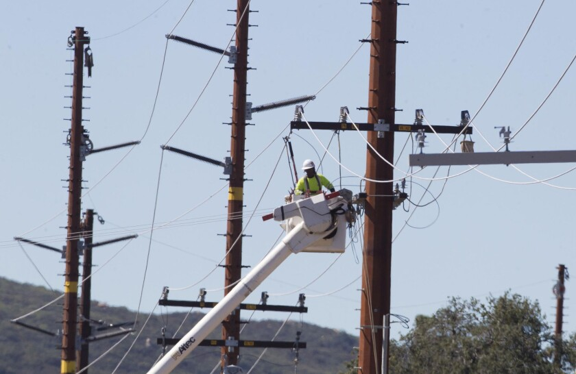 Utility crews work on power lines near state Route 79 in 2019.