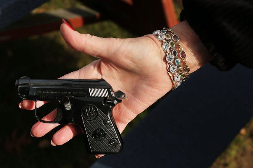 A woman holds a Beretta pistol at a gun buyback event at the Bridgeport Police Department's Community Services Division in Connecticut.