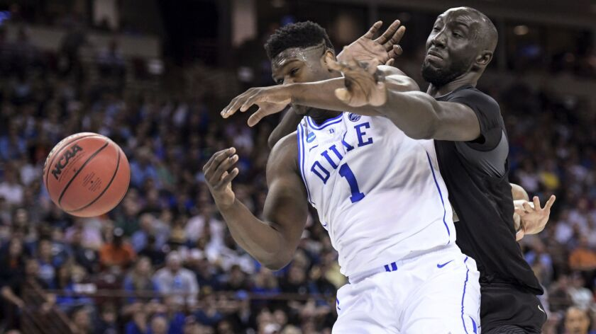 Central Florida center Tacko Fall, right, defends against Duke forward Zion Williamson during the first half of the Blue Devils' win in the second round of the NCAA tournament on Sunday.