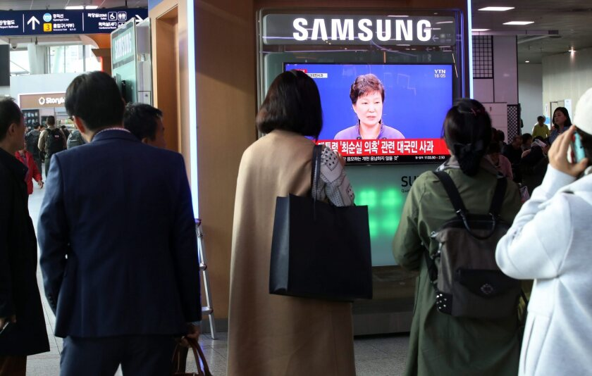 People watch South Korean President Park Geun-hye's live-aired public apology over the leak of confidential documents, including presidential speech drafts, Oct. 25 in Seoul.