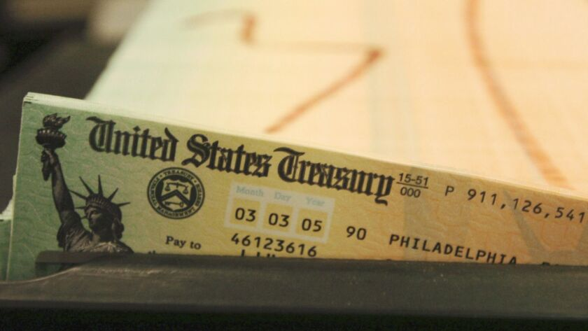 Social Security checks in a tray, shown in 2005, wait to be mailed out.