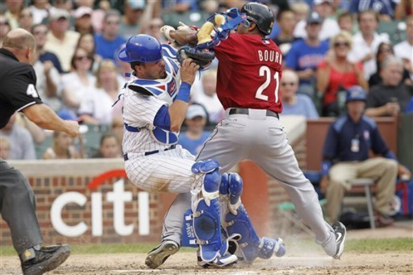 Houston Astros' Michael Bourn, right, slams into Chicago Cubs catcher Geovany Soto while trying to score on a ground ball hit by Hunter Pence during the fourth inning of a baseball game Monday, Sept. 6, 2010 at Wrigley Field in Chicago. Soto held onto the ball and Bourn was called out at home. (AP Photo/Brian Kersey)
