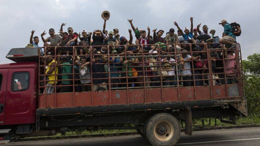 Central American migrants, part of the caravan hoping to reach the U.S. border, get a ride Nov. 2 on a truck in Donaji, Oaxaca state, Mexico.