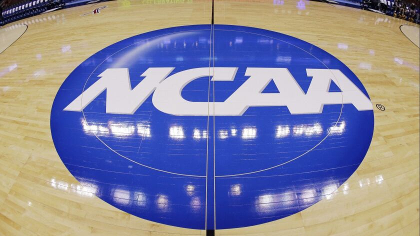 FILE - In this March 21, 2013, file photo taken with a fisheye lens, the NCAA logo is displayed at m