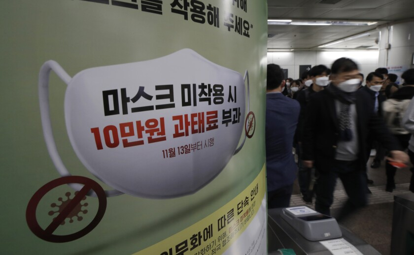 Gente con mascarilla para protegerse del coronavirus pasa junto a un cartel que avisa de multas de 90 dólares