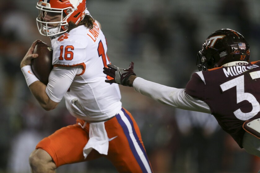 Clemson' Trevor Lawrence runs for a 17-yard touchdown past Virginia Tech's Brion Murray during the first quarter of an NCAA college football game Saturday, Dec. 5, 2020, in Blacksburg, Va. (Matt Gentry/The Roanoke Times via AP, Pool)