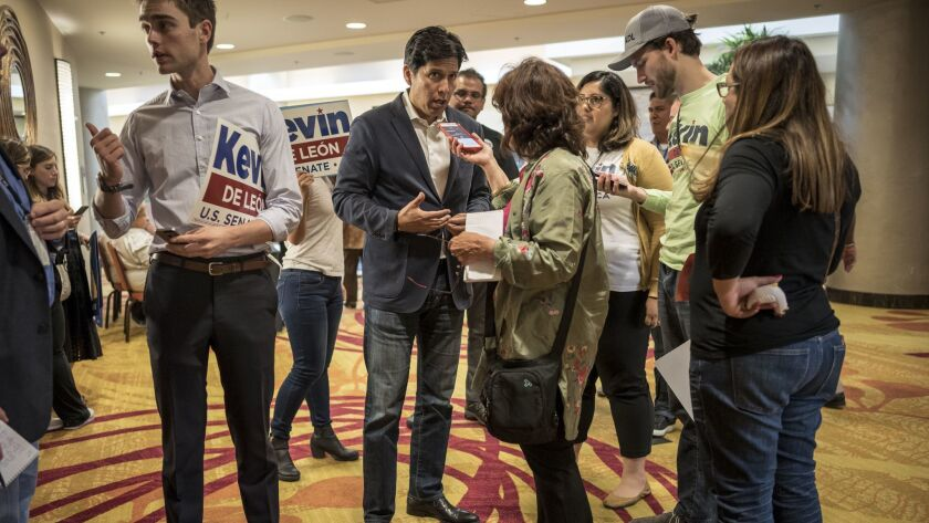 Kevin de Leon, center, speaks to reporters during Democratic state caucus meetings at the Marriot Hotel in downtown Oakland. Kevin de Leon and Diane Feinstein are competing for the endorsement of the California Executive Committee.