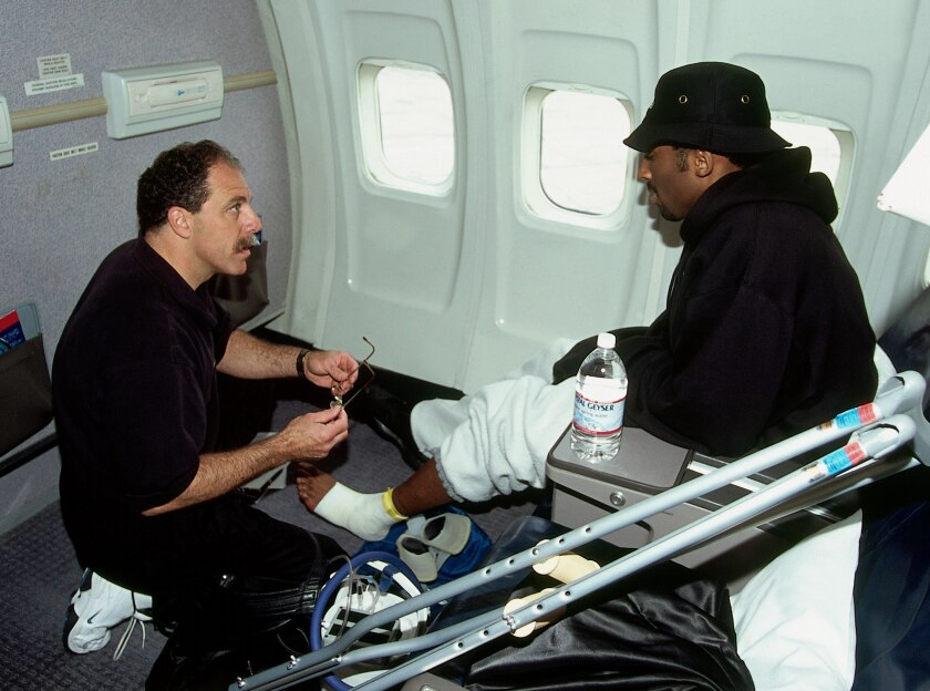 Gary Vitti treats Kobe Bryant on board the team flight to Indiana the day before Game 3 of the 2000 NBA Finals.