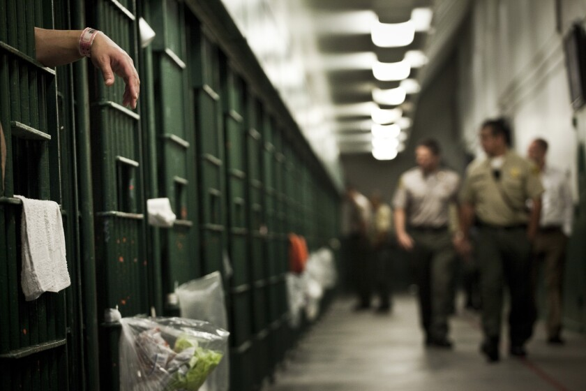 Deputies walk past cells at the L.A. County Men's Central Jail. County jails house 19,000 inmates.