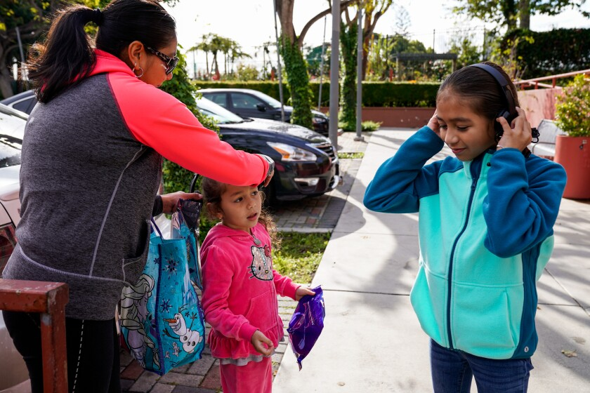 Gaby Regalado puts headphones on Jaqui Regalado, and Yuliana Regalado tries on hers at Mar Vista Family Center in April