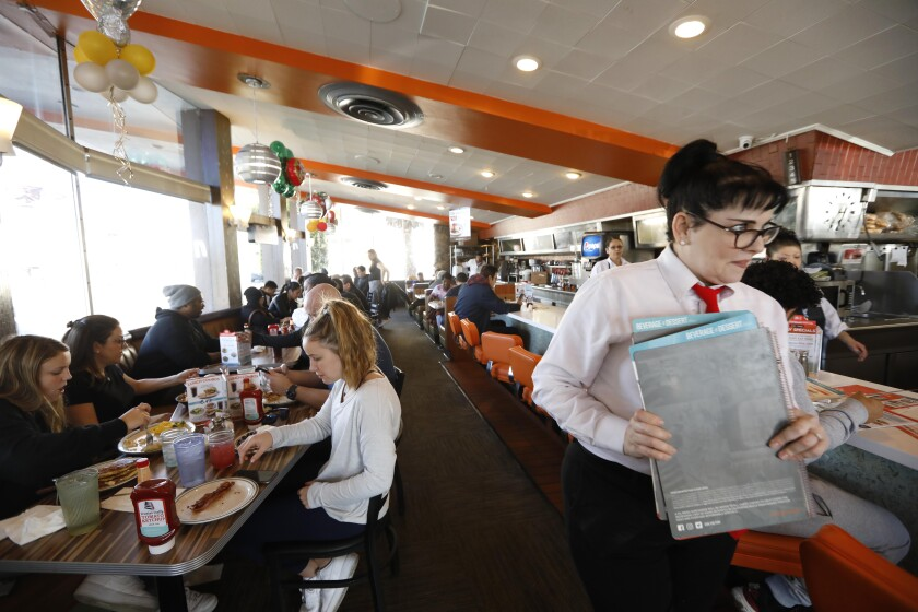 Hostess Hope Voedisch goes to greet customers at Norms.